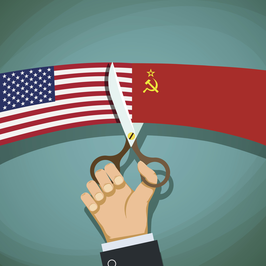 Hand with scissors cutting American flag away from USSR flag